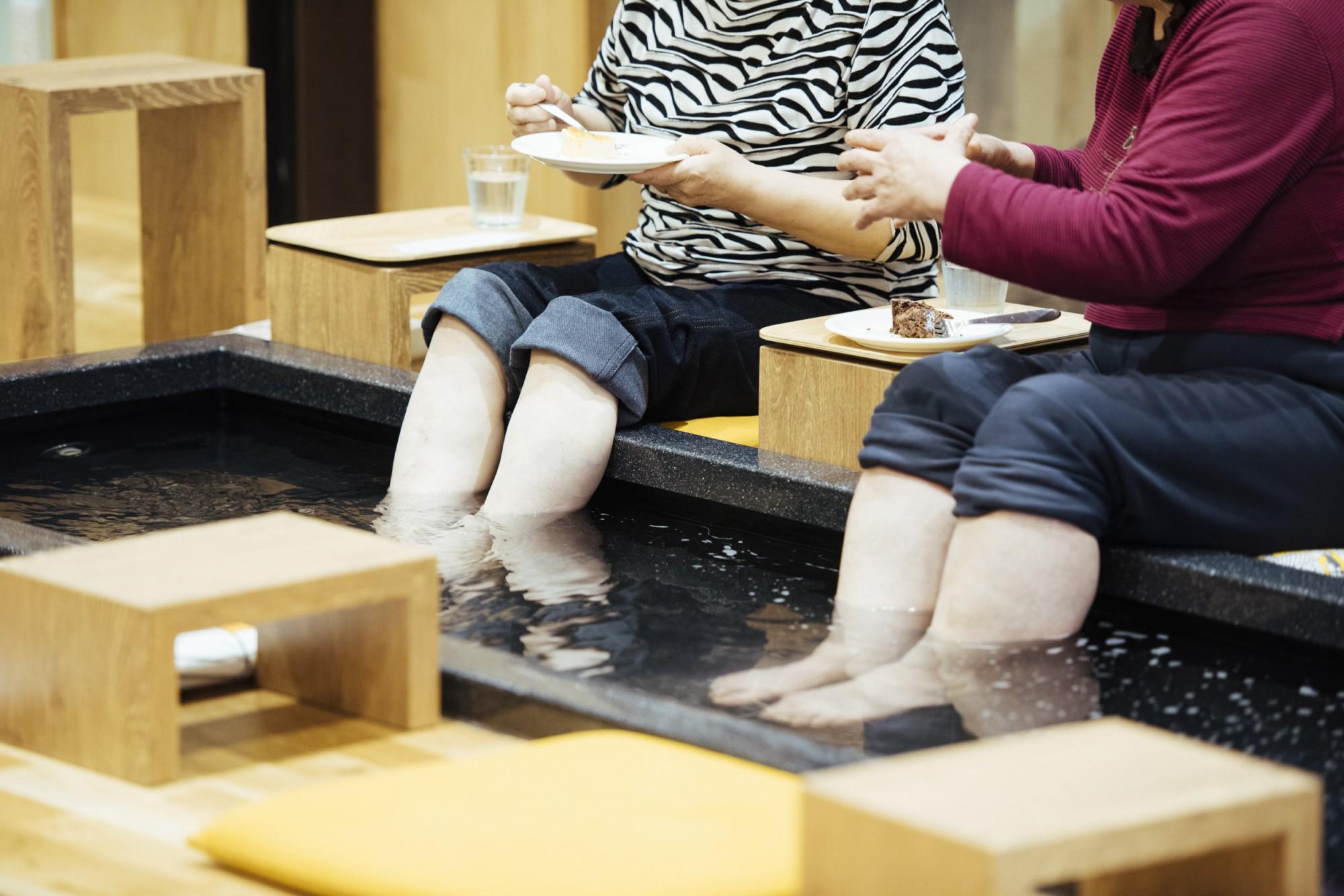 足湯につかりながらスイーツを楽しむお茶の時間。話が弾んで、つい長湯をしてしまうことも。