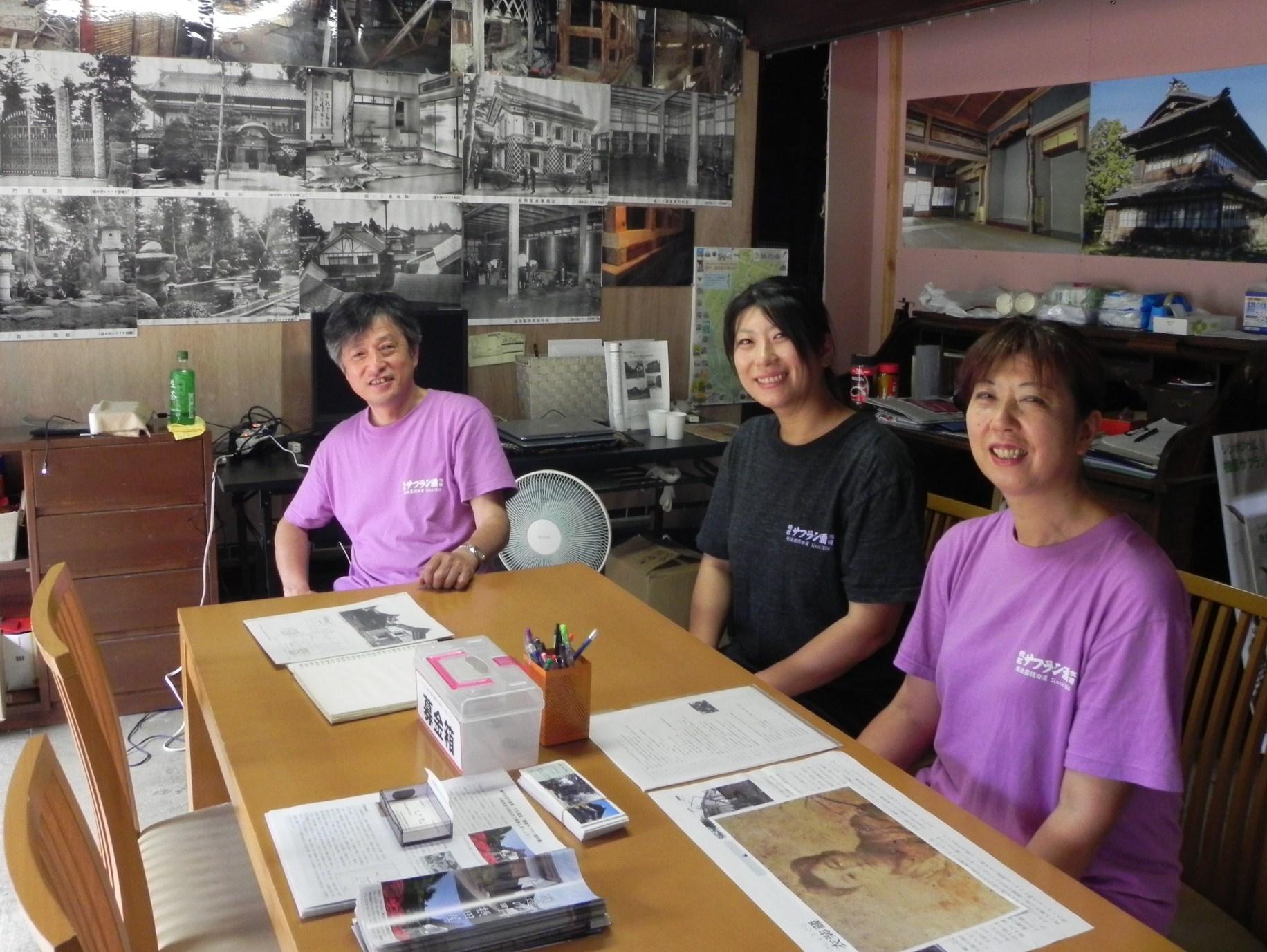 主屋に設けた休憩スペース。「見学お待ちしています」と事務局の平沢政明さん(左)と運営スタッフの皆さん。