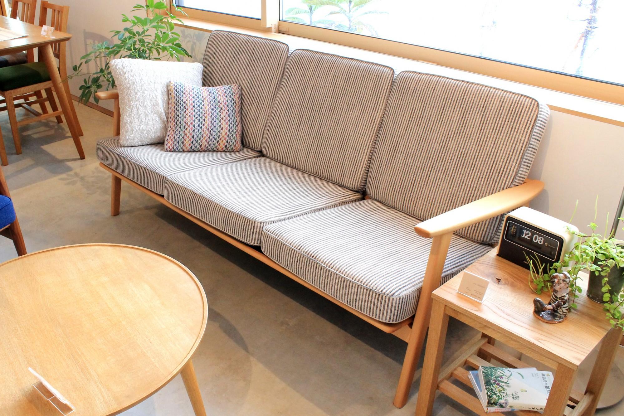 3人掛けのソファーは、生地に麻が入ったこだわりの手触り。オーダーごとに生地を取り寄せ、椅子張りしてもらっています。木部は、裕之さんの仕事です。