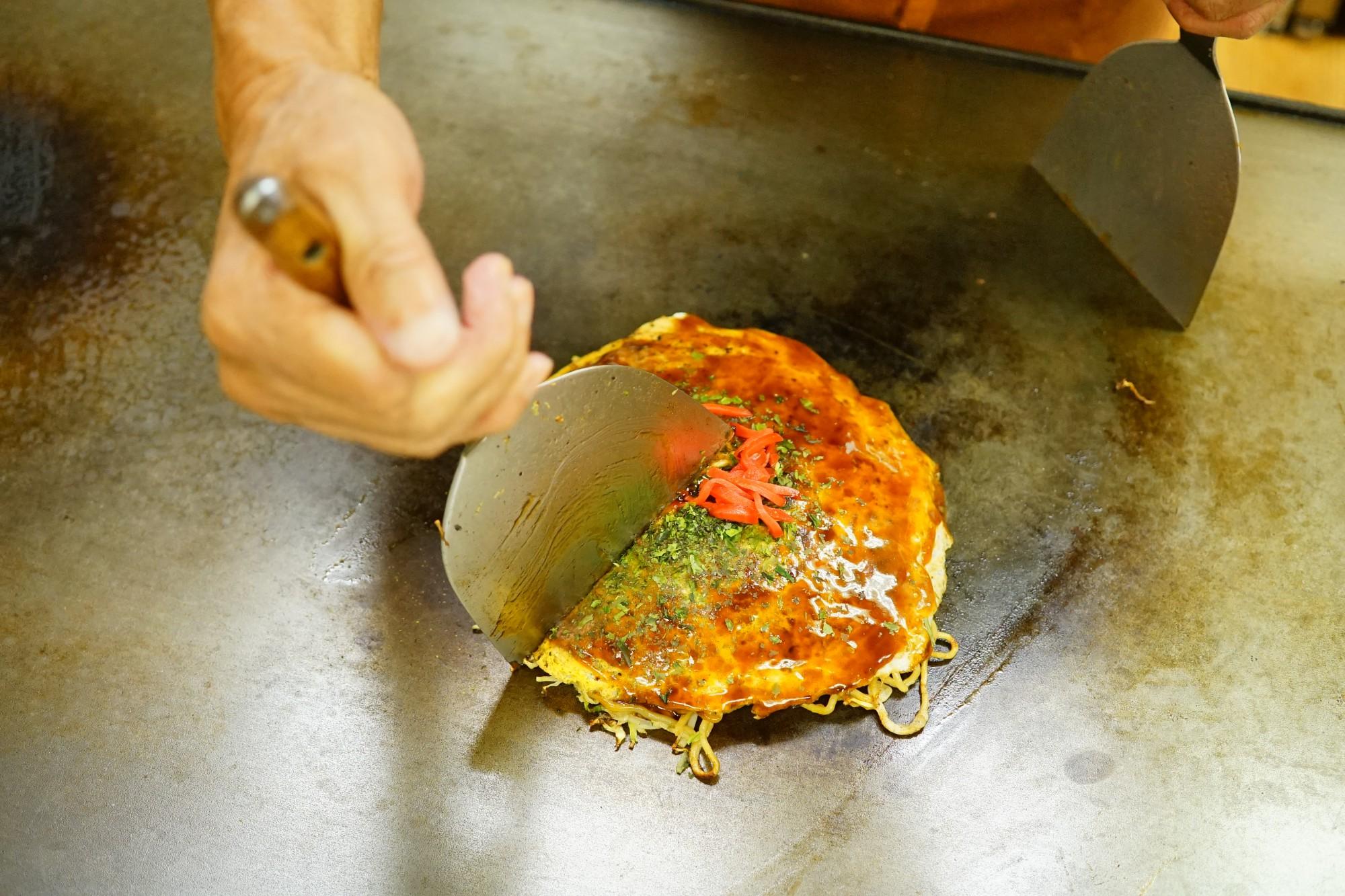 広島のお好み焼きは、薄めの生地にたっぷりと入った焼きそば、野菜が特徴。鉄板でご主人自ら焼いてくれる。