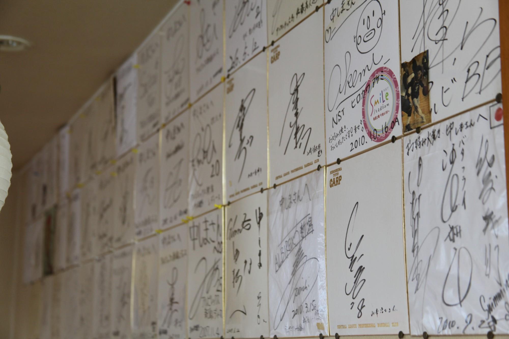 野球、サッカー、バスケットボール……。壁一面に飾られた色紙の多くがスポーツ選手のもの。