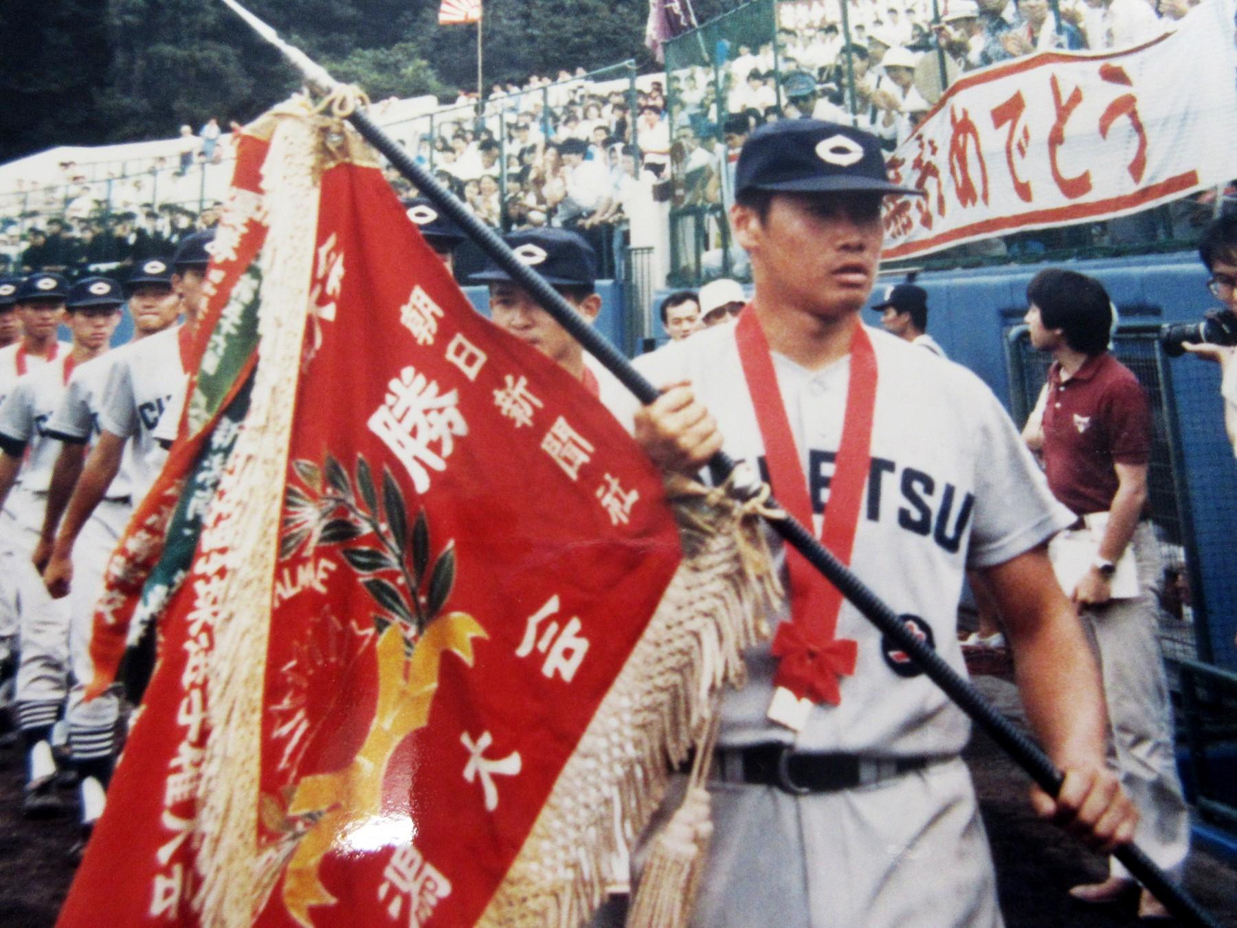 新潟県大会の優勝旗を手に球場を行進する主将・鈴木さんと中越高校チーム。